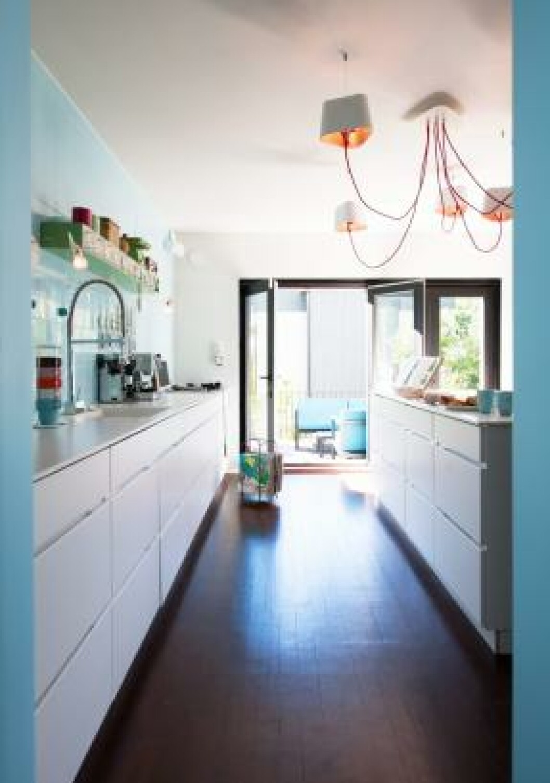 <strong>ÅPNET MOT UTEPLASSEN:</strong>  I enden av kjøkkenet er vinduene mot terrassen skiftet ut med foldedører slik at man har god kontakt med miljøet utenfor. Kjøkkeninnredningen er fra Kvik, taklampa fra Designheure.  Foto: Espen Grønli