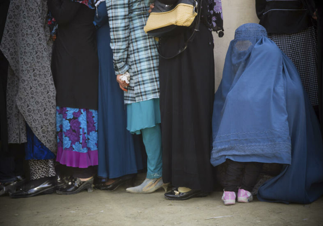 A child hides under his mother's burqa as women queue to get their registration card on the last day of voter registration for the upcoming presidential elections outside a school in Kabul, Afghanistan, Tuesday, April 1, 2014. Elections will take place on April 5, 2014. (AP Photo/Anja Niedringhaus)