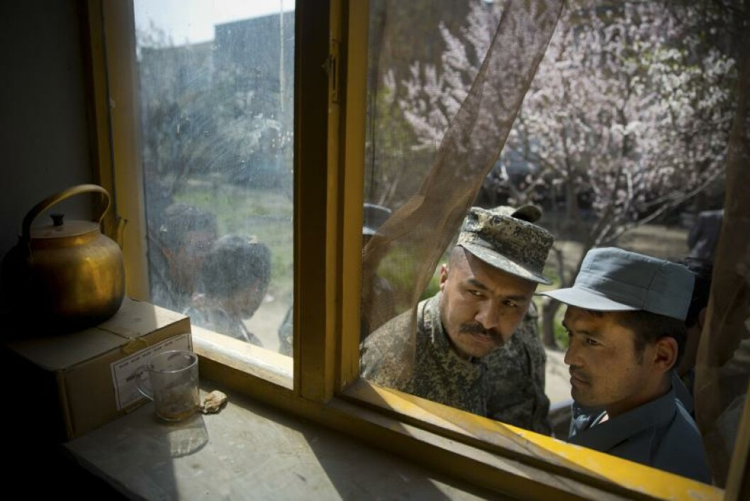 An Afghan soldier, left, and a police man peek through a window as they queue with others to get their registration card on the last day of voter registration for the upcoming presidential elections outside a school in Kabul, Afghanistan, Tuesday, April 1, 2014. Elections will take place on April 5, 2014. (AP Photo/Anja Niedringhaus)