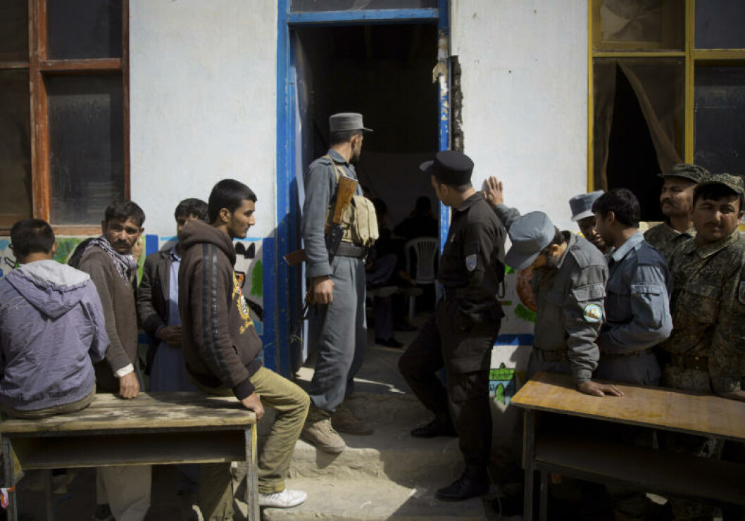 Afghan men wait in line to get their registration card on the last day of voter registration for the upcoming presidential elections outside a school in Kabul, Afghanistan, Tuesday, April 1, 2014. Elections will take place on April 5, 2014. (AP Photo/Anja Niedringhaus)