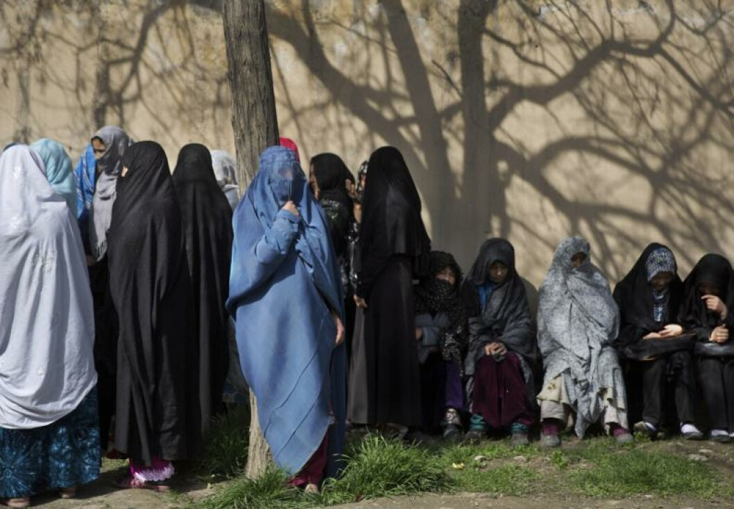 Afghan women wait under a tree to get their registration card on the last day of voter registration for the upcoming presidential elections outside a school in Kabul, Afghanistan, Tuesday, April 1, 2014. Elections will take place on April 5, 2014. (AP Photo/Anja Niedringhaus)