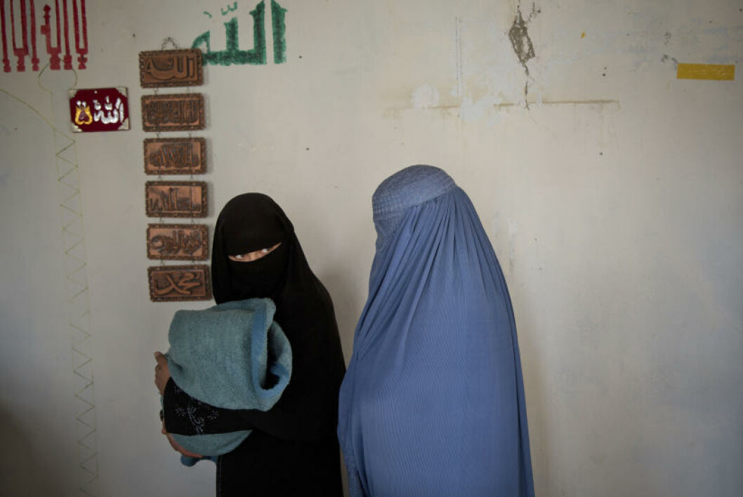 Afghan women with a child queue to get their registration card on the last day of voter registration for the upcoming presidential elections outside a school in Kabul, Afghanistan, Tuesday, April 1, 2014. Elections will take place on April 5, 2014. (AP Photo/Anja Niedringhaus)