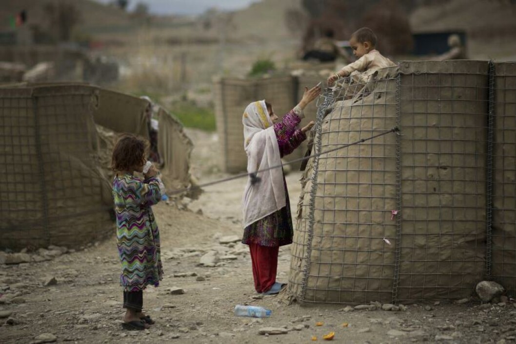 An Afghan girl helps her brother down from a security barrier set up outside the Independent Election Commission (IEC) office in the eastern Afghan city of Khost, Thursday, April 3, 2014. Afghan's go to the polls to elect a new President on April 5, 2014. (AP Photo/Anja Niedringhaus)