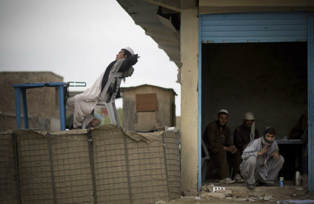 Afghan election workers take a tea break while a security guard stretches in the afternoon sun outside the Independent Election Commission (IEC) office in the eastern Afghan city of Khost, Thursday, April 3, 2014. Afghans go to the polls to elect a new President on April 5, 2014. (AP Photo/Anja Niedringhaus)