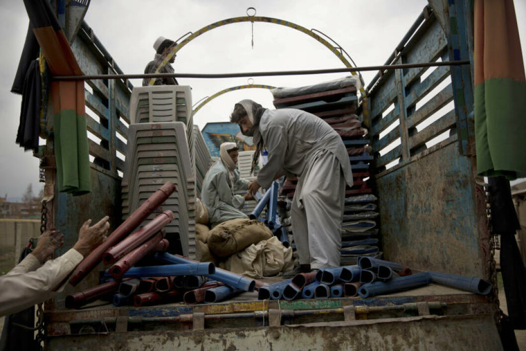 Afghan men load up a truck with office supplies and election materials to be delivered to election centers throughout the province in the eastern Afghan city of Khost, Thursday, April 3, 2014. Afghans go to the polls to elect a new President on April 5, 2014.  (AP Photo/Anja Niedringhaus)