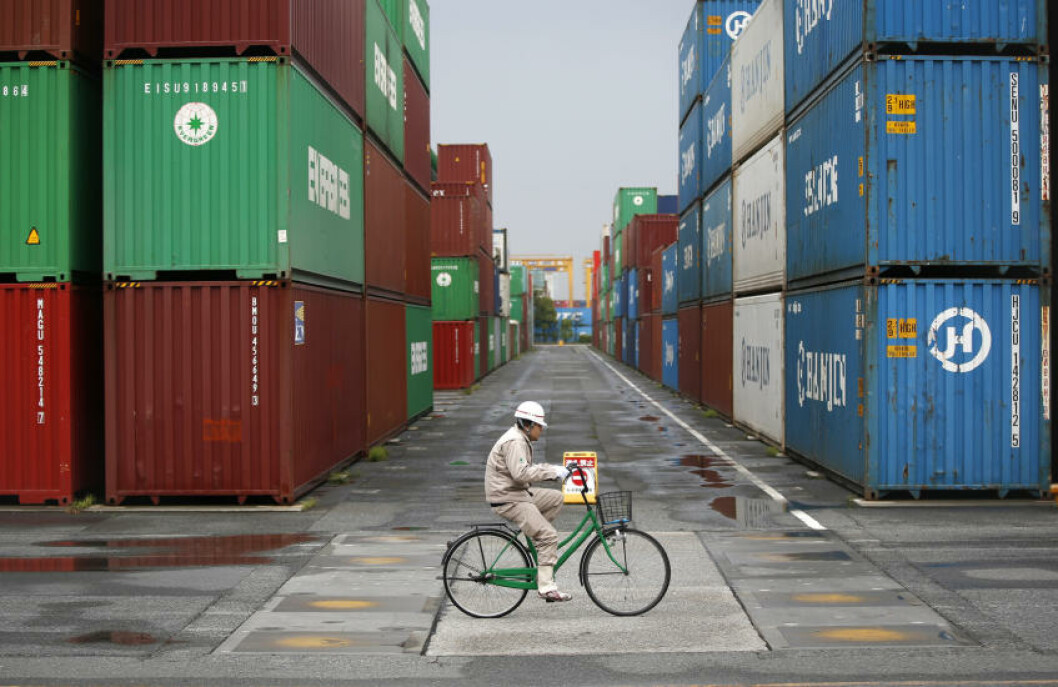 <strong>UTE Å SYKLE:</strong> En arbeider sykler gjennom et havneområde i Tokyo. Japan sliter med et stadig økende handelsunderskudd, og mars var verste måned på lang tid. Foto: Toru Hanai / Reuters / NTB Scanpix