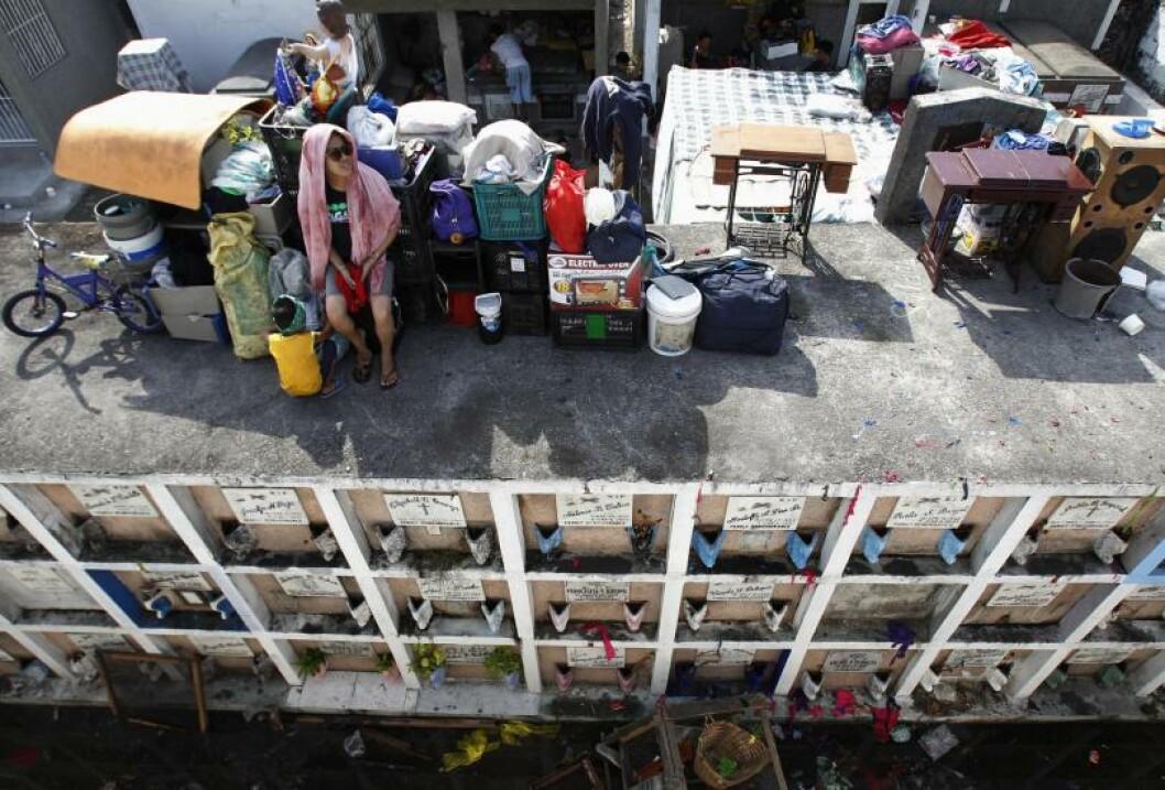 <strong>MISTET HJEMMET:</strong> En kvinne vokter sine eiendeler fra sitt nye bosted på toppen av en gravplass utenfor Manila. En brann i et slumoråde førte til at en person mistet livet og over 1000 familier mistet sitt hjem. Foto: Romeo Ranoco / Reuters/ NTB Scanpix