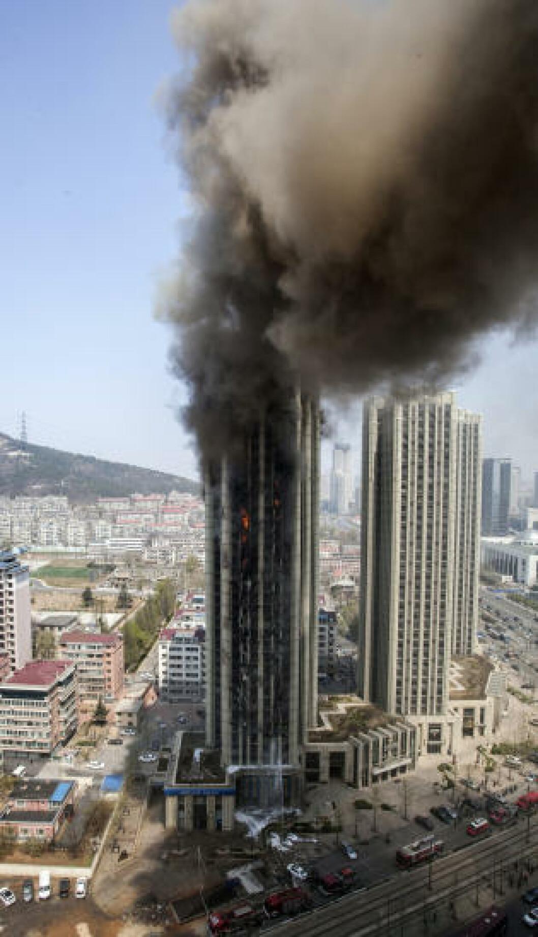 <strong>BRANN I HØYBLOKK:</strong> Røyken stiger fra en boligblokk i Dalian i Kina. Brannen ble slokket, og det er ikke meldt om skadde. Foto: China Daily/ Reuters/ NTB Scanpix.