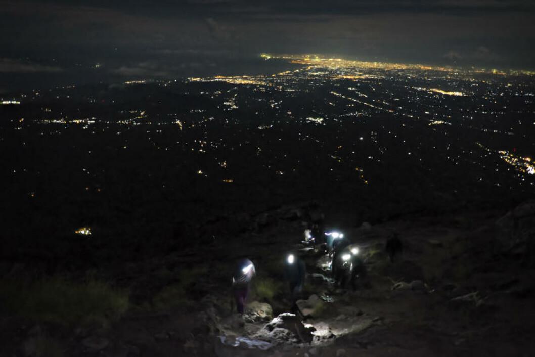 BY I DET FJERNE: Som ildfluer beveger vi oss sakte oppover vulkansiden, mens lysene fra Denpasar lyser opp horisonten. Foto: ANITA ARNTZEN