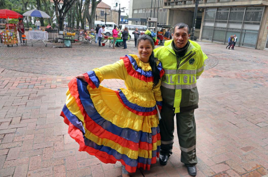 <strong>PASSER PÅ:</strong> En kvinne i typisk colombiansk drakt poserer i Bogota sentrum. Politiet er aldri langt unna. Denne konstabelen syntes det var stas å bli med på bildet. Foto: EIVIND PEDERSEN
