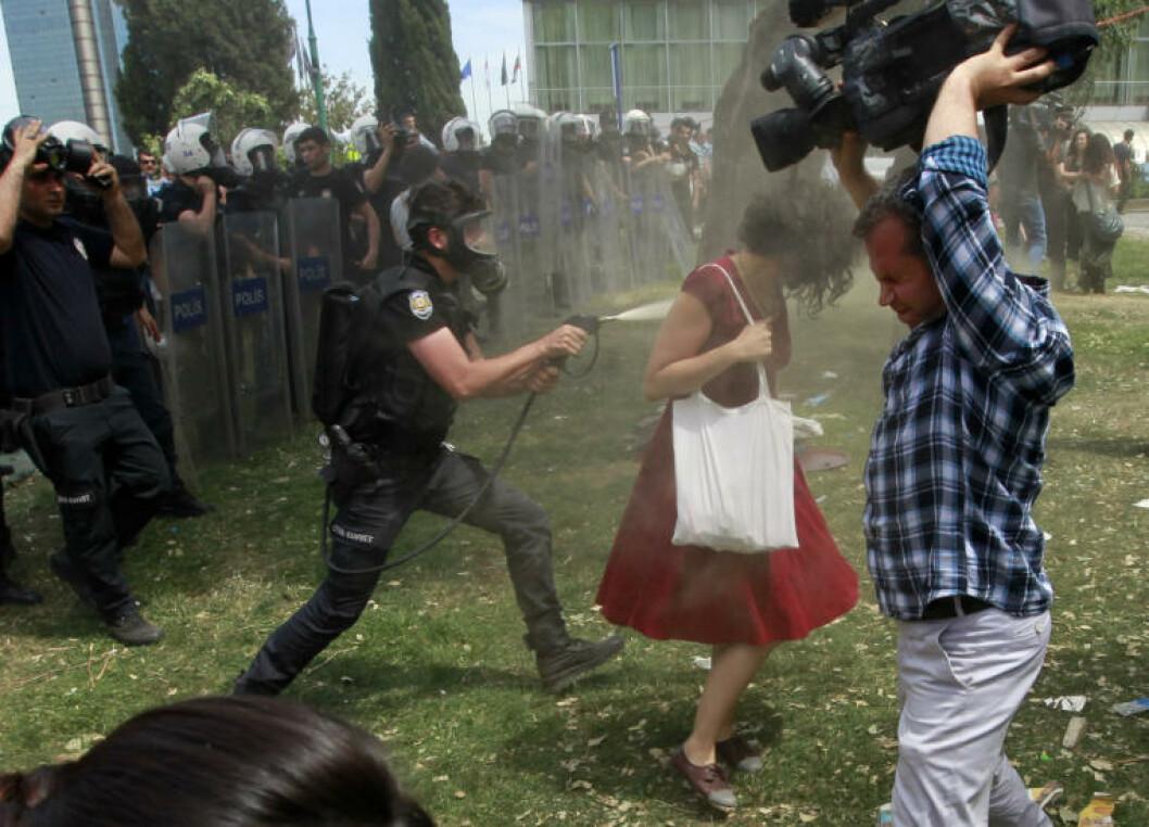 <strong>VEKK:</strong> Den unge kvinnen går vekk, og blir fortsatt dynket av politimannen på plassen i Istanbul. Kameramannen må holde opp videokameraet sitt, for å unnslippe gassregnet. Foto: Osman Orsal / Reuters / NTB Scanpix