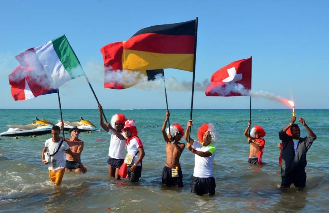 <strong>SAMLET:</strong> Turister fra flere land samlet seg 29. juni på stranda i Sousse for å hedre de som mistet livet og for å vise at de fortsatt vil støtte turismen i Tunisia. Foto: AFP PHOTO / FETHI NASRI / NTB Scanpix