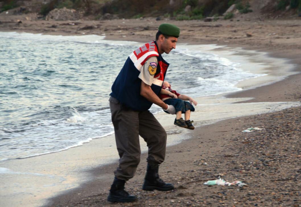 <strong>ENDA ET OFFER:</strong> Treåringen bæres vekk fra vannet an uniformert mann. Foto: AP Photo/DHA/NTB Scanpix